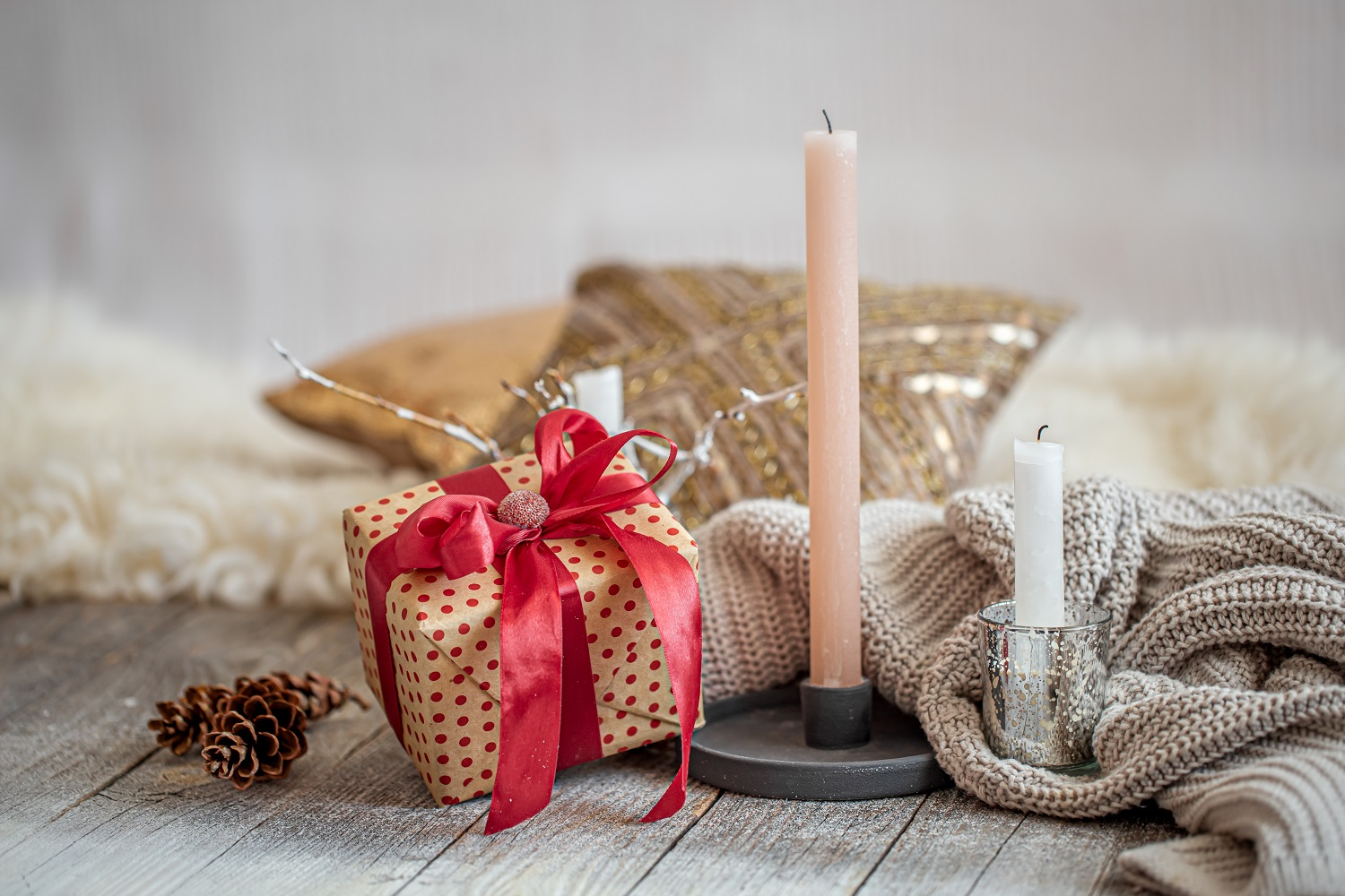 Cozy festive still life with a gift and a candle on a wooden table. The festive concept.