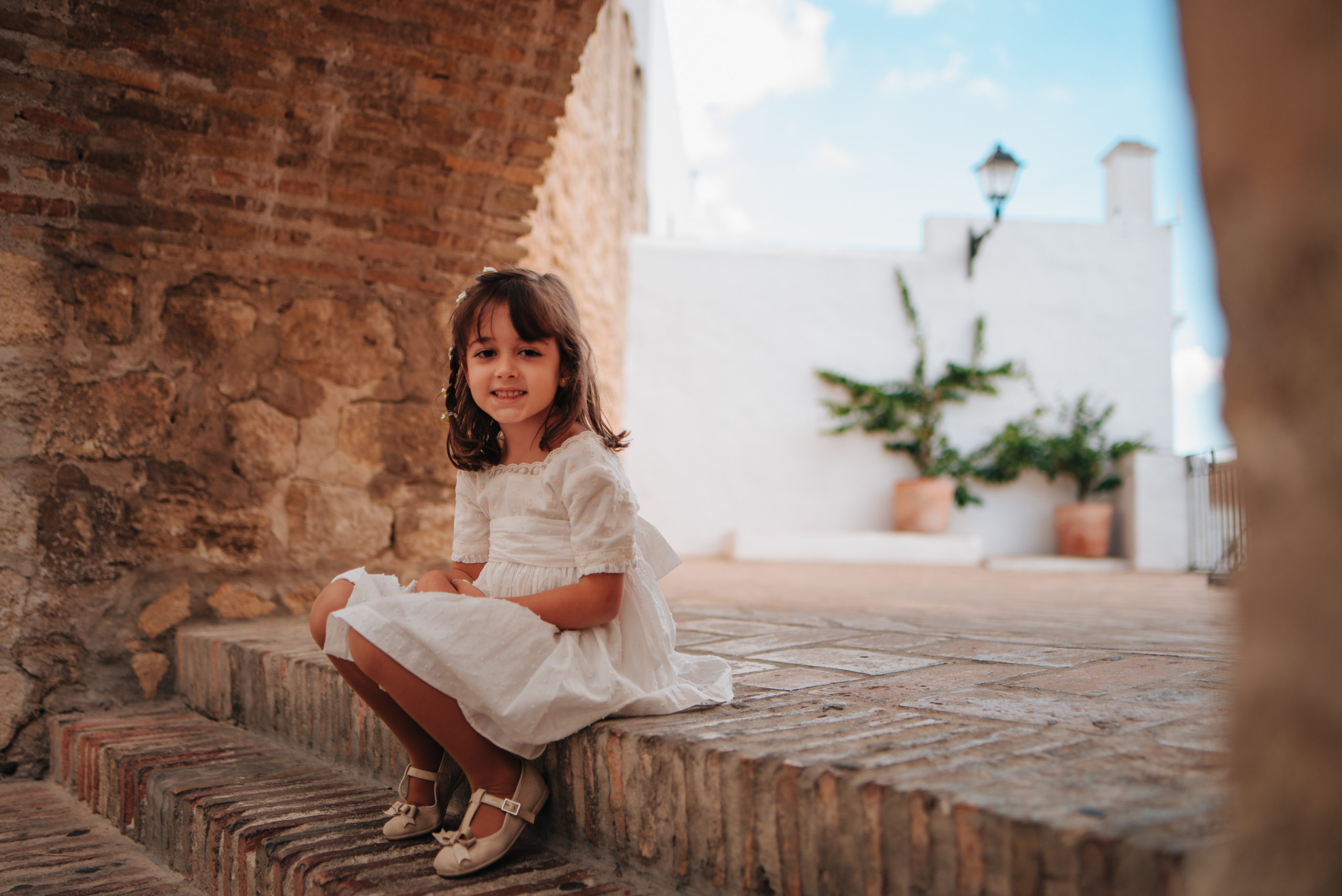 Smiling Caucasian girl with brown hair sitting on a stone staircase